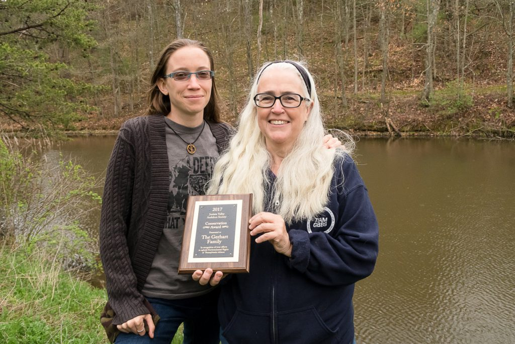 Two women holding an award plaque next to a pond